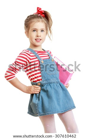 Adorable little grey-eyed girl with long hair tied with a red bow. The girl is dressed in a short denim skirt and striped sweater. Girl holding under his arm a thick book . Closeup-Isolated on white - stock photo