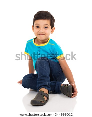adorable little indian boy sitting on the floor - stock photo