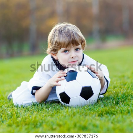 Adorable little kid boy  having fun with playing soccer with football on field, outdoors. In white German national uniform. Happy child about european championship - stock photo