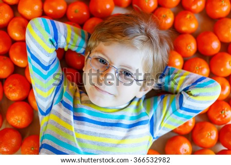Adorable little kid boy wearing eye glasses with mandarin oranges background. Happy smiling child with lot of fruits. Healthy food, eating and lifestyle concept. - stock photo