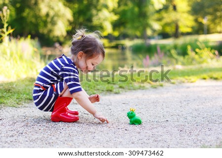 Adorable little princess girl in red rain boots playing with rubber toy frog. Outdoors. Fairytale concept - stock photo