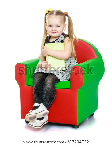 Adorable little round-faced girl with pigtails on her head sitting on a chair hugging hands book-Isolated on white background - stock photo