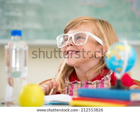 Adorable little school blonde girl sitting in school - stock photo