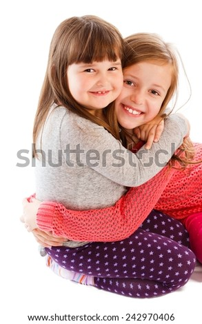 Adorable little sisters showing love to each other, hugging. - stock photo