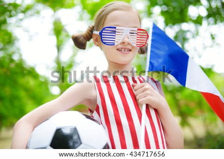 Adorable little soccer fan cheering on summer day - stock photo