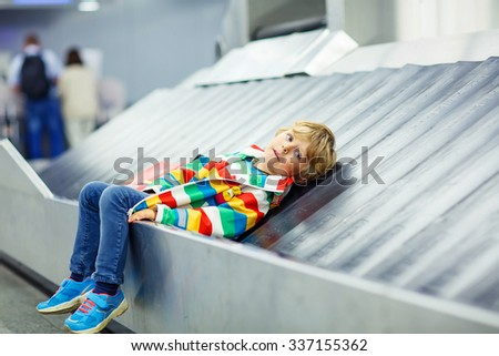 Adorable little tired kid boy at the airport, traveling. Upset child waiting with kids suitcase on baggage carousel. Canceled flight due to pilot strike. - stock photo