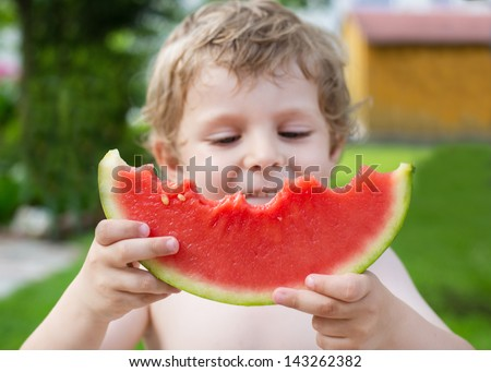 Adorable little toddler boy with blond hairs eating watermelon in summer garden. Selective focus on watermelon