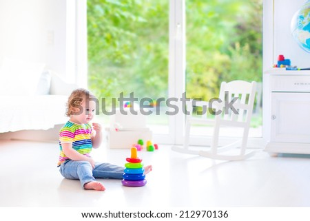 Adorable little toddler girl in a colorful shirt playing with a toy pyramid and construction blocks sitting on the floor in a white sunny bedroom  with big garden view windows - stock photo