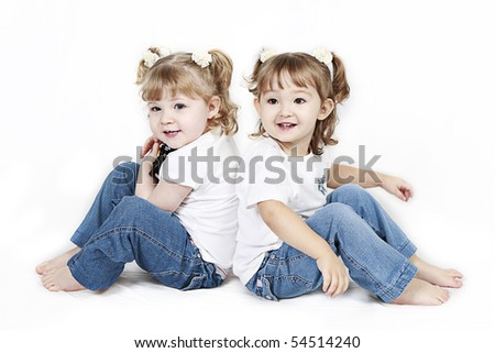Adorable little twin girls isolated on white background - stock photo