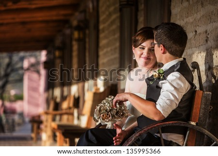 Adorable loving lesbian couple sitting on bench - stock photo