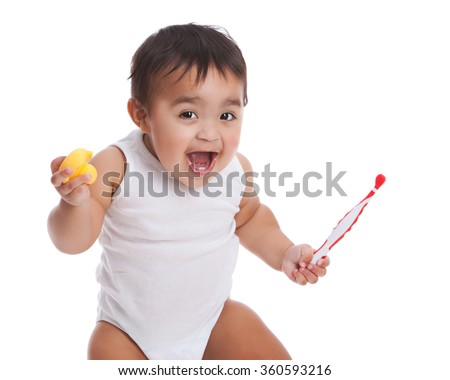 Adorable mixed race baby boy holding an infant toothbrush and rubber duckie.  Isolated on white. - stock photo