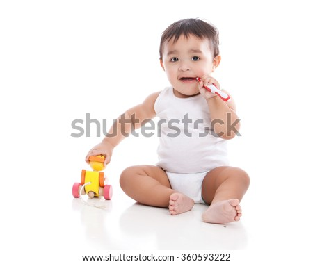Adorable mixed race boy brushing his teeth while playing with a wooden duck.  Isolated on white.