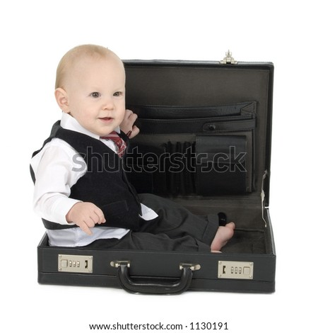 Adorable 10 month old baby boy in business suit, barefoot, sitting in empty briefcase. Shot in studio over white.