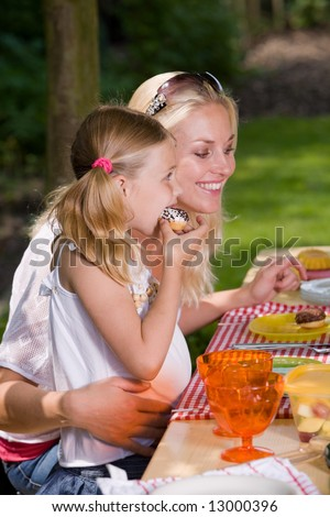 Adorable mother and daughter eating something outside on a summer's day - stock photo