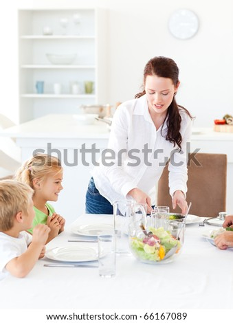 adorable mother serving salad to her children for lunch standing in the kitchen