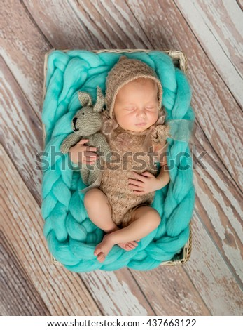 adorable newborn baby in costume with bunny-toy in cot top view - stock photo