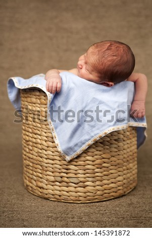 Adorable newborn baby sleeping in a baboo basket - stock photo