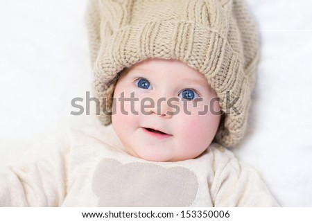 Adorable newborn baby wearing a big knitted hat and a warm sweater relaxing on a white blanket