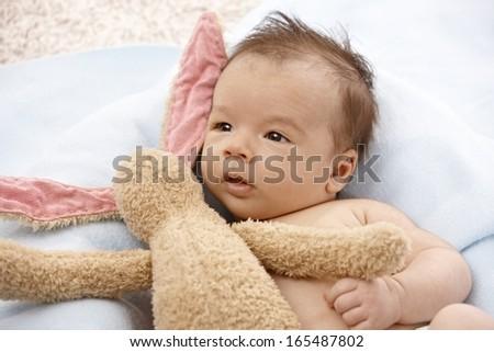 Adorable newborn baby with plush bunny. - stock photo