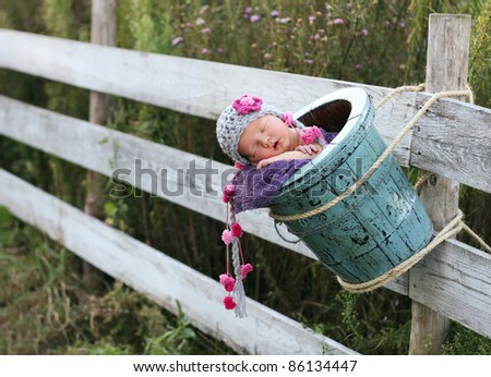 Adorable newborn in a bucket, outside hanging on a fence - stock photo
