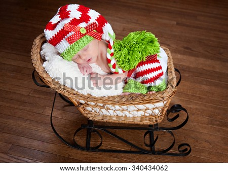 Adorable newborn wearing a red, white and green striped hat and leggings - fast asleep in a little sled.  - stock photo