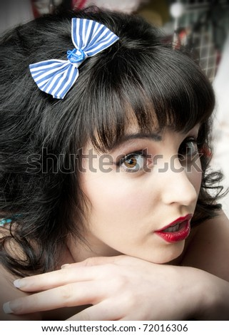 Adorable pinup model wearing blue anchor hair bow - stock photo