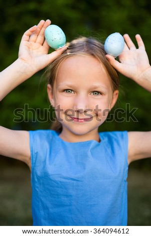 Adorable playful little girl with colorful Easter eggs outdoors at spring - stock photo