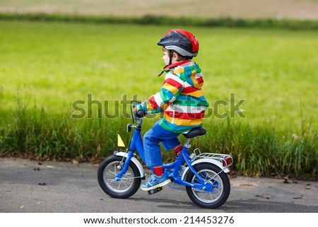 Adorable preschool boy in red safety helmet and colorful raincoat riding his first bike on summer day. - stock photo