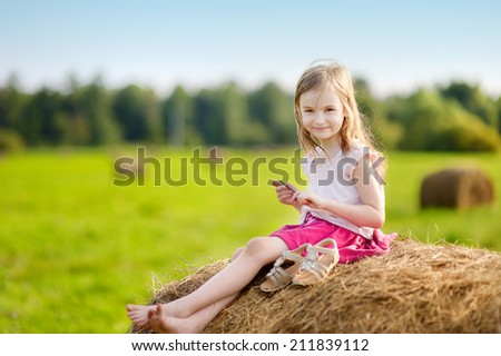 Adorable preschooler girl sitting on a haystack in wheat field on warm and sunny summer day - stock photo