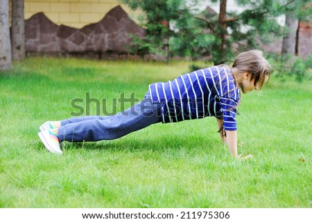 Adorable preteen girl doing exercise outdoors on the lawn - stock ...