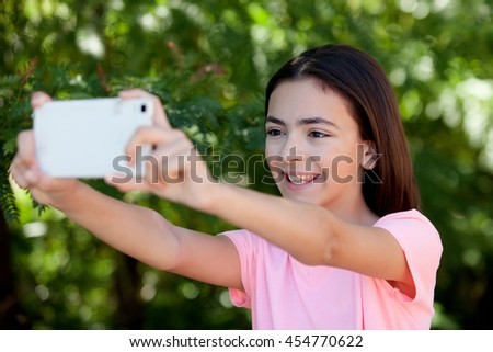Adorable preteen girl with mobile with plants of background - stock photo