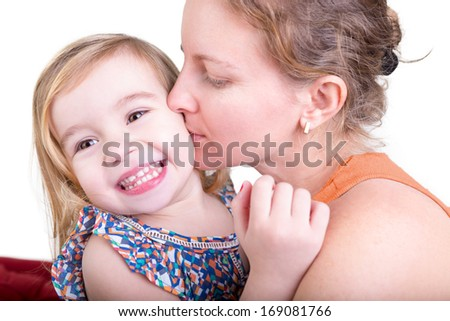 Adorable pretty little blond girl laughing as she is kissed on the cheek by her beautiful young mother - stock photo