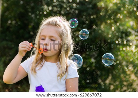adorable school age girl blowing bubbles outside
