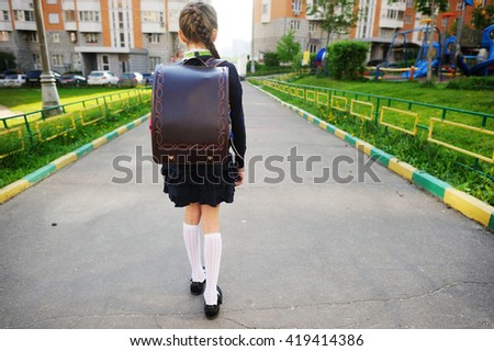Adorable school aged  girl with backpack outdoor in the park