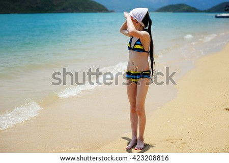 Adorable school aged  kid  girl having fun  on beach vacation