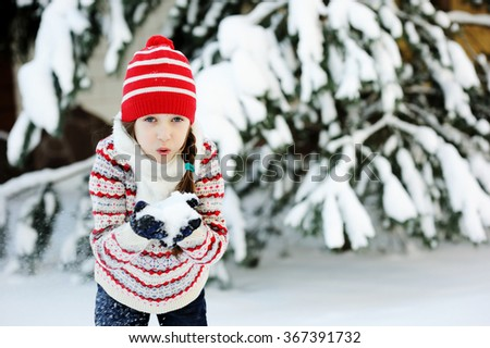 Adorable school aged kid girl in colorful sweater and hat playing in the snow on beauty winter day - stock photo