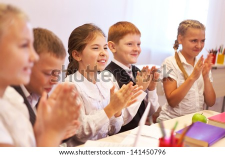 Adorable schoolgirl  looking on something during break of lesson - stock photo