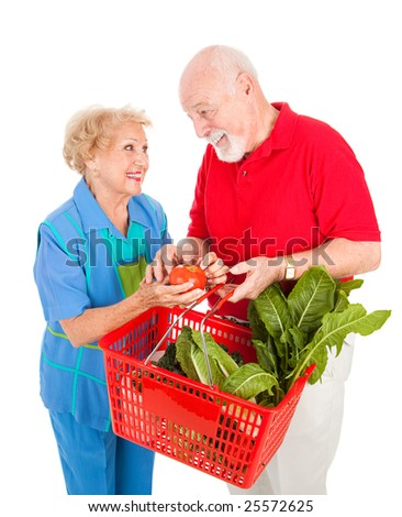 Adorable senior couple enjoys shopping for healthy fresh produce together.  Isolated on white.