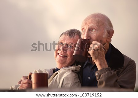 Adorable senior couple outdoors drinking from mugs - stock photo