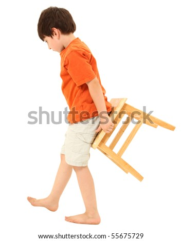 Adorable seven year old boy carrying a stool behind him. - stock photo