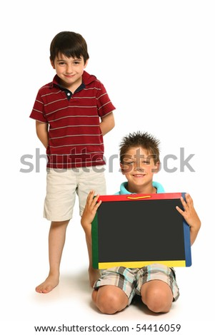 adorable seven year old boys with blank chalk board