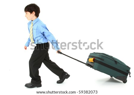 Adorable seven year old french american boy pulling large suit case over white background. - stock photo