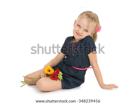 Adorable, shy little girl with short blonde bangs on her head is sitting on the floor in a short blue dress. The girl thoughtfully sitting on the floor resting on her knees a bouquet of colorful - stock photo
