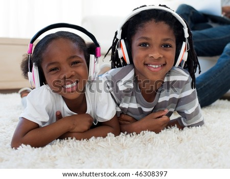 Adorable siblings listening music in the living room - stock photo