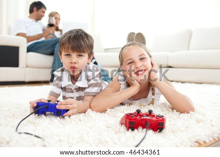 Adorable siblings playing video games lying on the floor