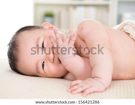 Adorable six months old Asian baby girl lying on bed biting fingers. - stock photo
