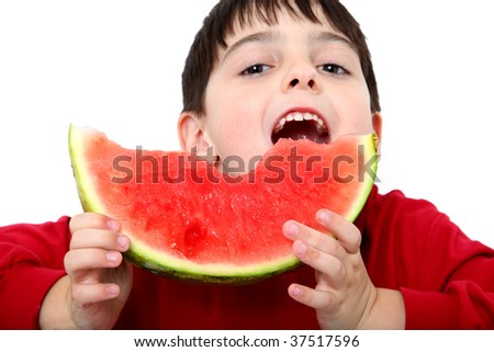 Adorable six year old boy eating sliced watermelon.