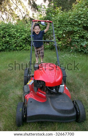 Adorable six year old boy mowing his lawn with push mower. - stock photo