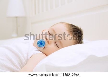 Adorable sleeping baby on the pillow with pacifier, close up indoors shot   - stock photo