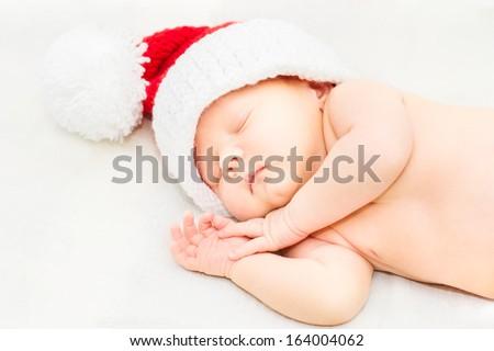Adorable sleeping newborn baby wearing Santa Claus hat, Christmas, New Year - stock photo